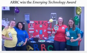 Four members of the team next to their booth containing information about product and promotional material