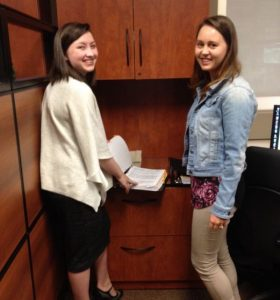 Two ABT grads doing admin work looking at a file