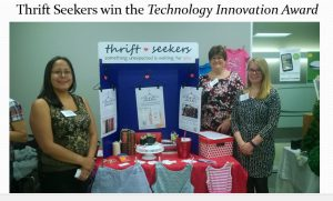 Three members of the team next to their booth containing information about product and promotional material
