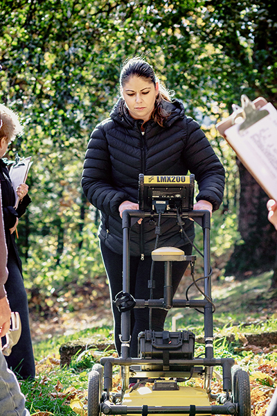 Photo of Dr. Sarah Beaulieu pushing a Ground Penetrating Radar machine in a wooded area, while people with clipboards observe and take notes.