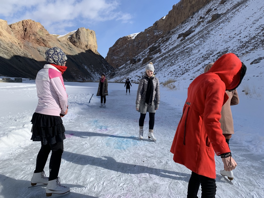 Photo of Chelsea Novakowski and Afghan women skating outdoors on a snow-covered frozen lake, with brown stone cliffs in the background.