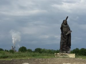 Standing Bear Monument with refinery stacks in the background