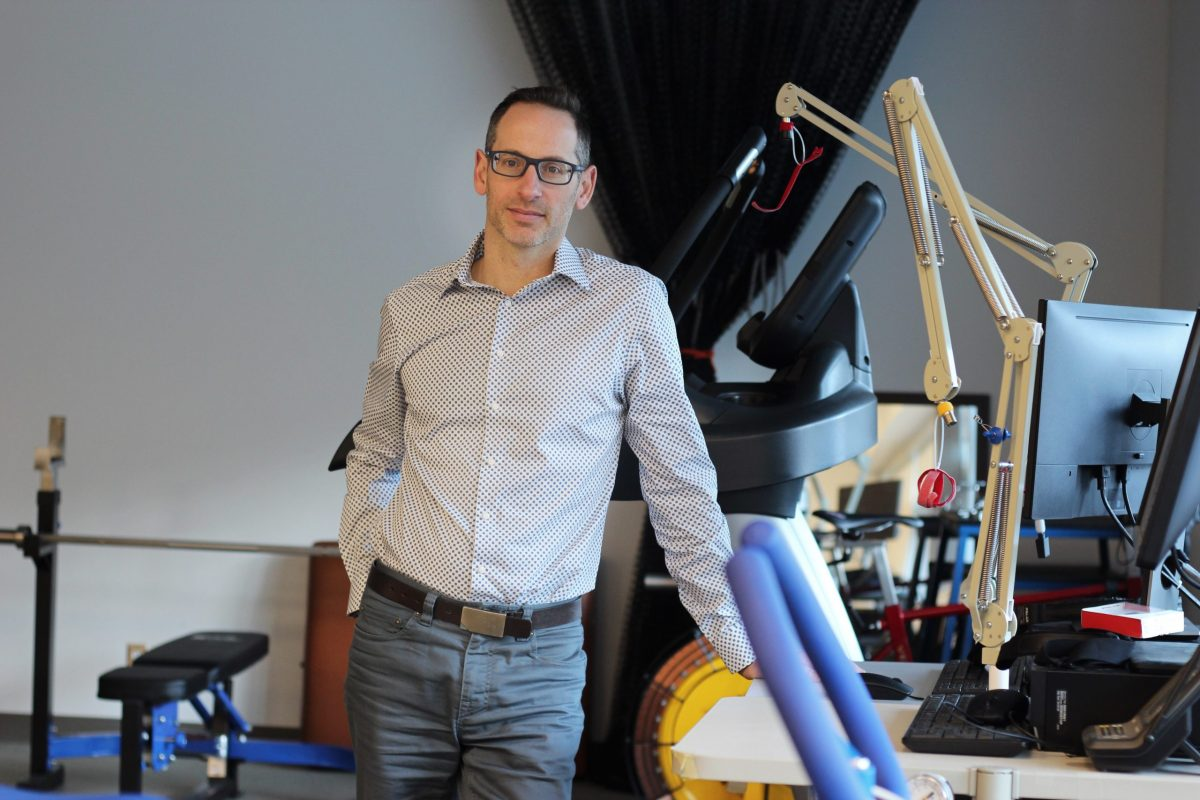 Dr. Jason Brandenburg stands next to kinesiology equipment