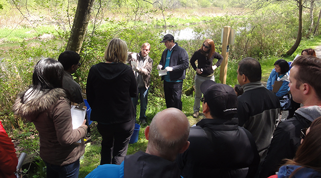 UFV geography instructor Scott Shupe discusses water collection with volunteers, including the president of HSBC Bank of Canada.