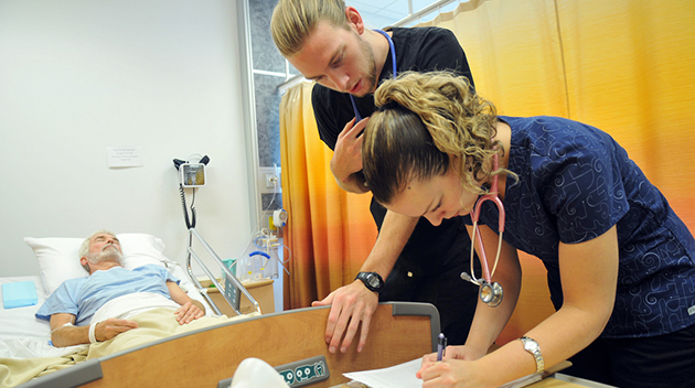 While Dr. Alan Quinn acts as a patient in the background, nursing students Johan Bergenhenegouwen and Ashley Ketler make notes in his chart.