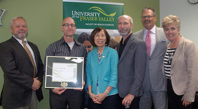 Dr. Michael Gaetz of the Kinesiology and Physical Education department received the UFV Research Excellence award for 2014. Pictured with Gaetz (holding award) are UFV President Mark Evered; Adrienne Chan, Associate VP of Research, Engagement, and Graduate Studies; Provost and VP Academic Eric Davis; UFV Board of Governors Second Vice Chair Randy Bartsch; and Dean of Health Sciences Joanne MacLean.