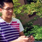 UFV student playing Pokemon GO near Marina Magnone Memorial Tree